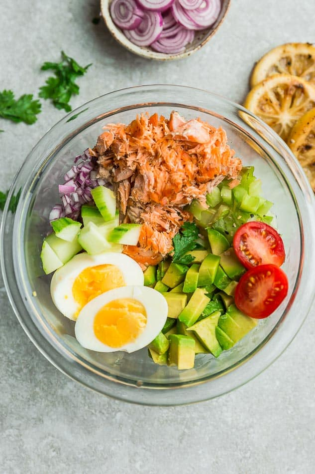 Top view of ingredients to make salmon salad in a clear bowl on a grey background with lemon, oninos, celery, avocado, egg, salmon and Whole30 mayo