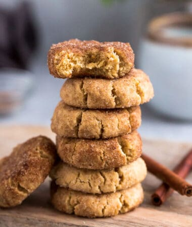 Side view of 6 stacked low carb paleo soft snickerdoodle cookies on a wire rack on a grey background with a bite