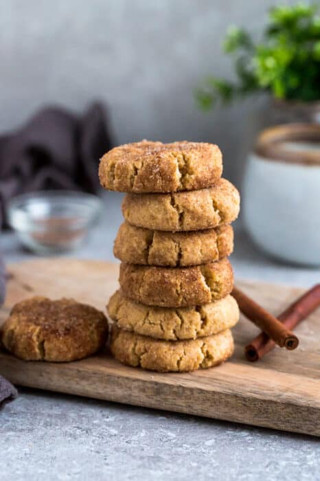 Side view of 6 stacked low carb paleo soft snickerdoodle cookies on a wire rack on a grey background
