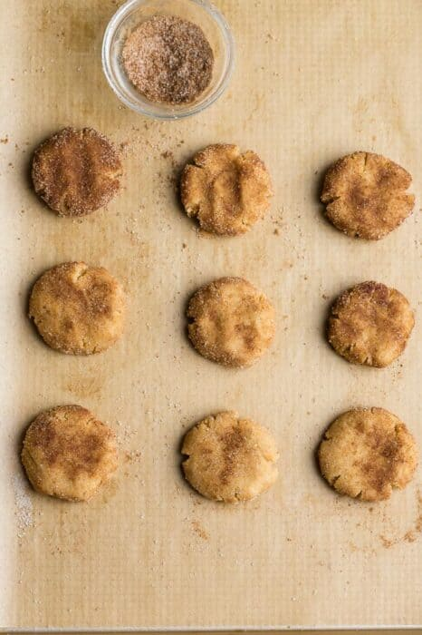 Top view of 9 unbaked low carb snickerdoodle cookie dough on parchment paper on a baking sheet