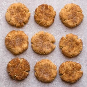 Top view of 9 keto snickerdoodles on a grey background