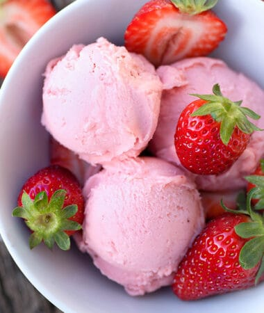 Top view of 3 scoops of low carb keto strawberry ice cream in a white bowl with fresh strawberries on a wooden background