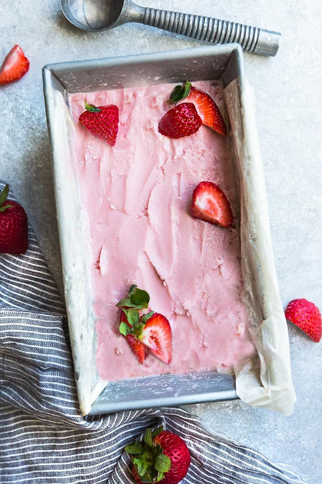 Top view of low carb keto strawberry ice cream in a silver loaf pan with an ice cream scoop and fresh strawberries on a grey background