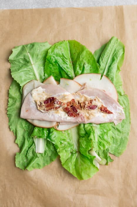 Top view of lettuce layered with turkey, ham and mayonnaise on a brown parchment paper.