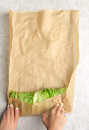 Top view of hands rolling a low carb lettuce wrap sandwich using brown parchment paper