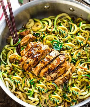 Top close-up view of Low Carb Zucchini Noodles with Chicken in a stainless steel pan on a wodden board with chopsticks