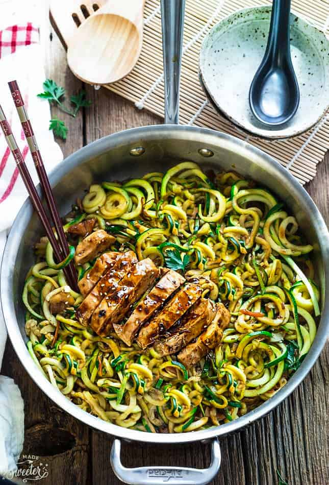 Top view of Low Carb Zucchini Noodles with Chicken in a stainless steel pan on a wodden board with chopsticks