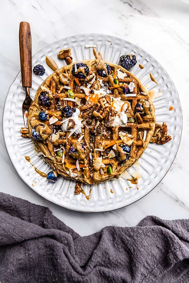 1 Belgian Waffle with blackberries and coconut cream on a white plate with a fork