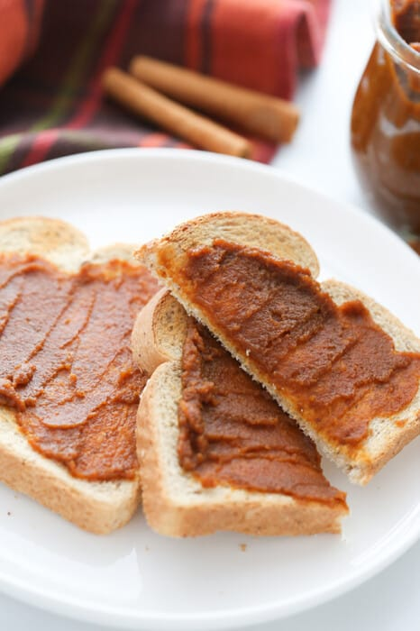 Side view of low carb pumpkin spread on toast on a white plate