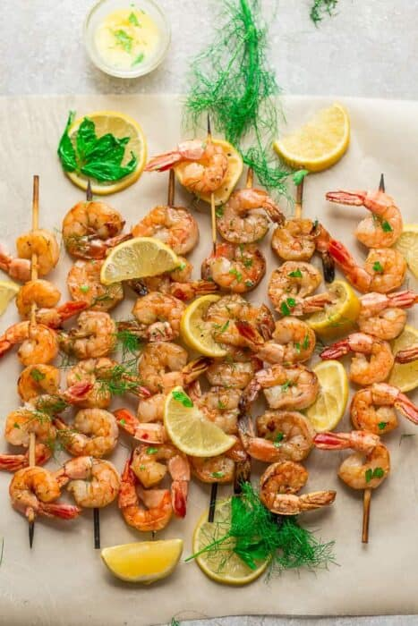 Top view of grilled shrimp for shrimp salad on a parchment paper on a grey background