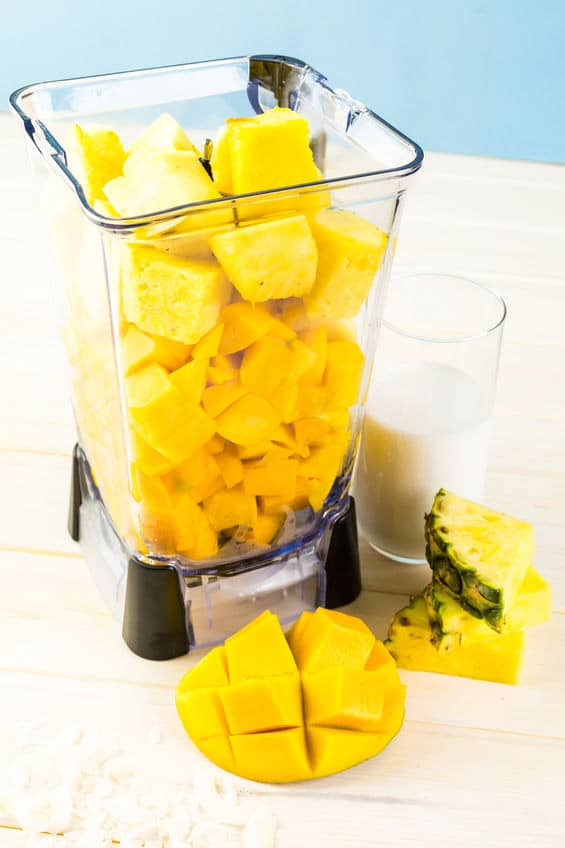Chopped mango and pineapple in a blender to make a mango smoothie