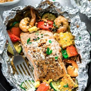 Top view of a foil packet with Mediterranean salmon with shrimp and vegetables