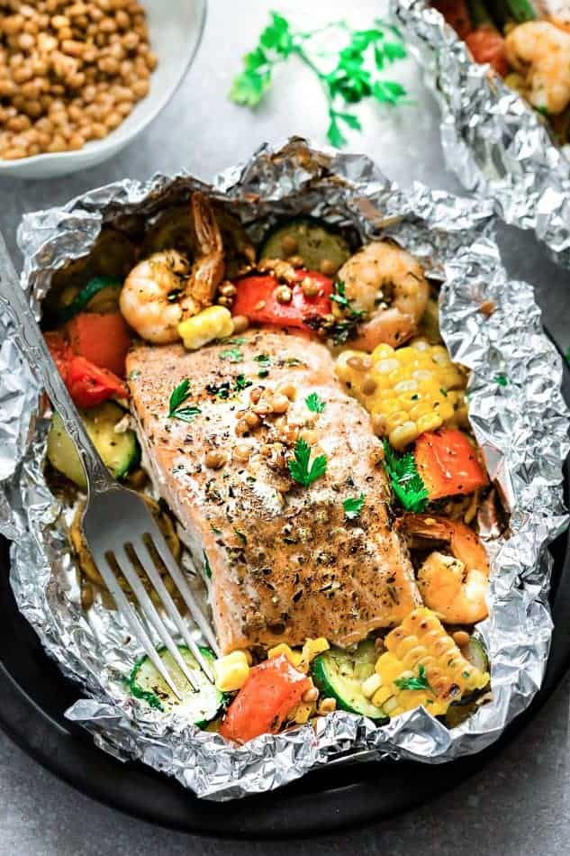 Top view of a foil packet with Mediterranean salmon surrounded by shrimp and vegetables