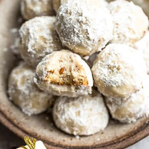 Close up top view of a pile of vegan Mexican Wedding cookies with one Russian tea cake with a bite in a brown bowl