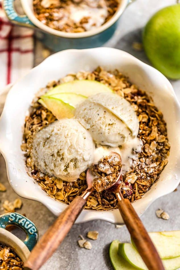 a white scalloped edge bowl with warm cinnamon apple crisp, ice cream and 2 spoons