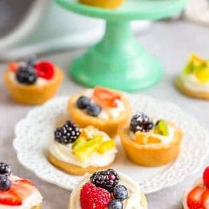 A Mini Fruit Pizza with other fruit pastries on and around a plate