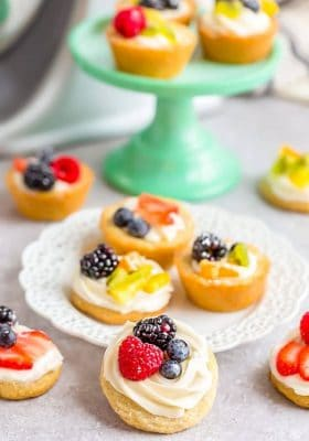 Mini Fruit Pizza desserts scattered on and around a dessert plate