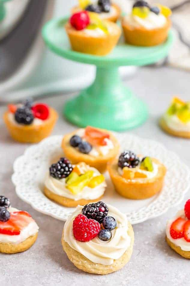 Mini Fruit Pizzas scattered on and around a dessert plate