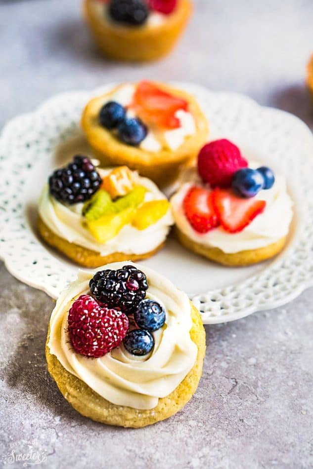 Mini Fruit Pizza - a classic dessert made using homemade soft sugar cookies topped with fresh fruit. Perfect for spring or summer barbecues, potlucks, showers, and parties. Best of all, no dough chilling required and easy to customize! Use a mix of fresh strawberries, blueberries, blackberries, raspberries, kiwi, mandarin oranges or pineapples!