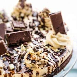 A whole Mint Andes Chocolate Brownie Cheesecake on a plate topped with chocolate drizzle and Andes Mint candies