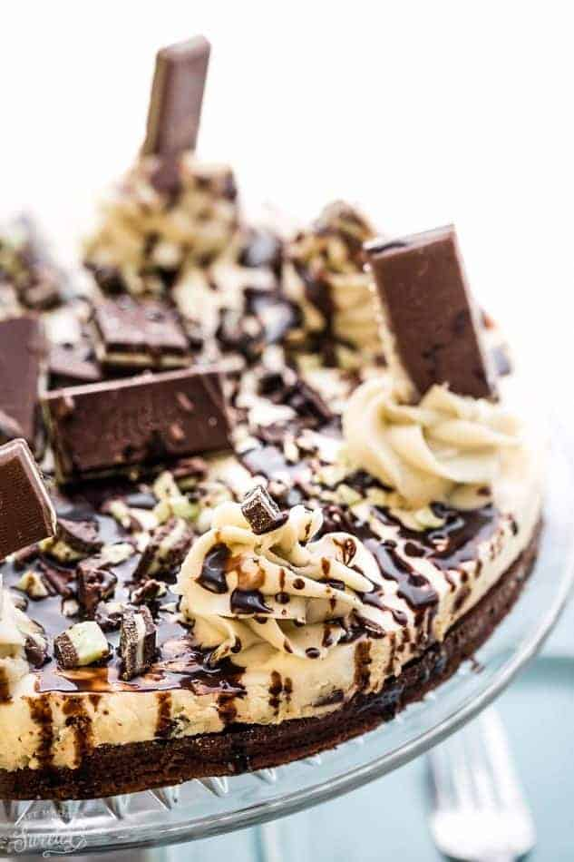 Whole Andes Mint Chocolate Brownie Cheesecake topped with chocolate drizzle and Andes Mint candies on a plate