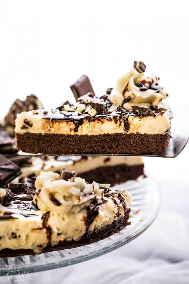 A whole Mint Andes Chocolate Brownie Cheesecake with a slice on a spatula