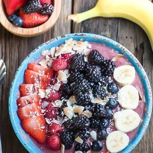 Top view of a Mixed Berry Detox Smoothie Bowl next to berries and a banana