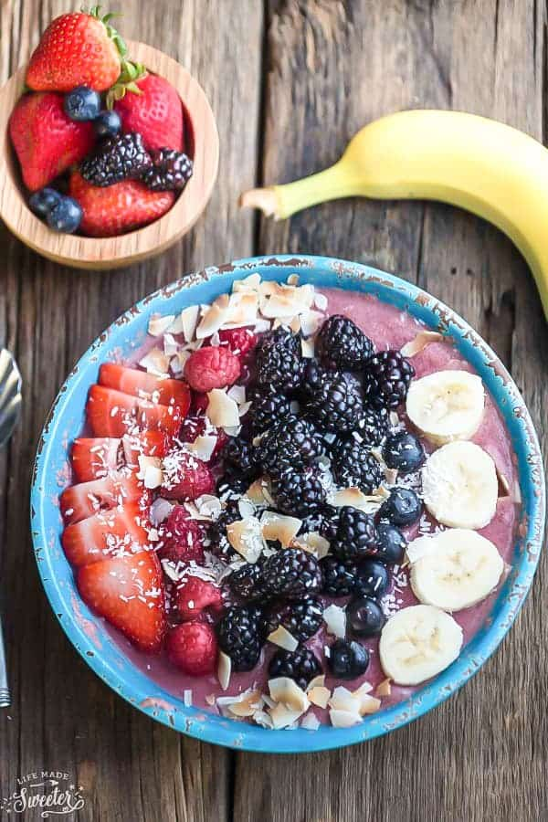 Top view of mixed berry smoothie bowl topped with fresh strawberries, raspberries, blackberries, blueberries, bananas, and coconut flakes.