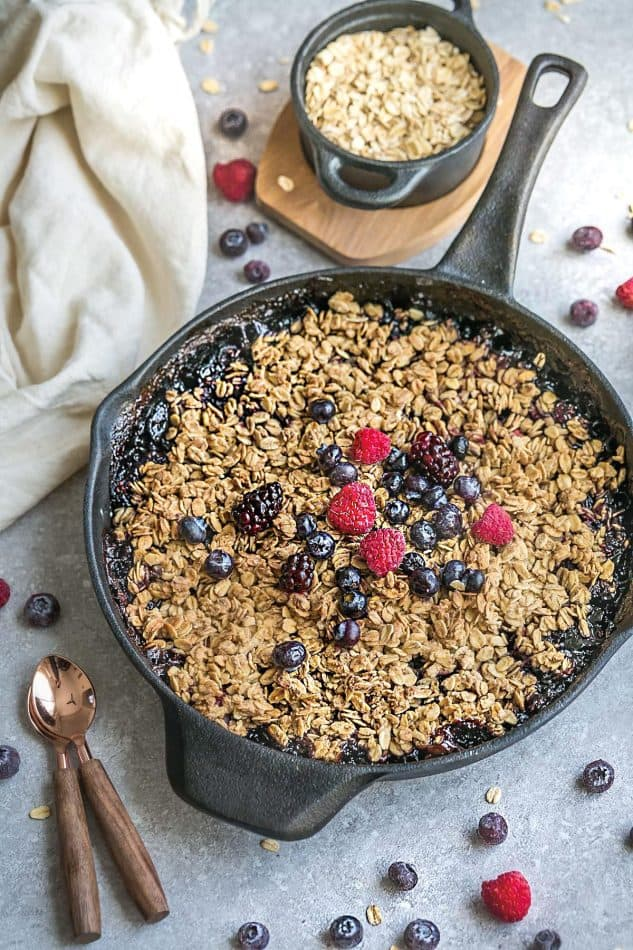 Berry skillet crisp in dark skillet on grey surface with fresh berries and oats.