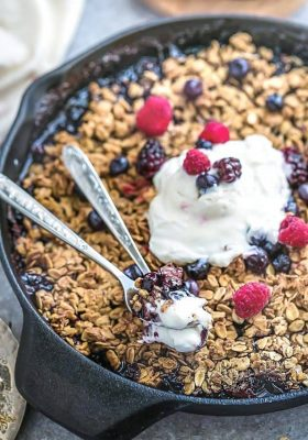 Easy Mixed Berry Skillet Crisp in a cast iron skillet with vanilla ice cream on top.