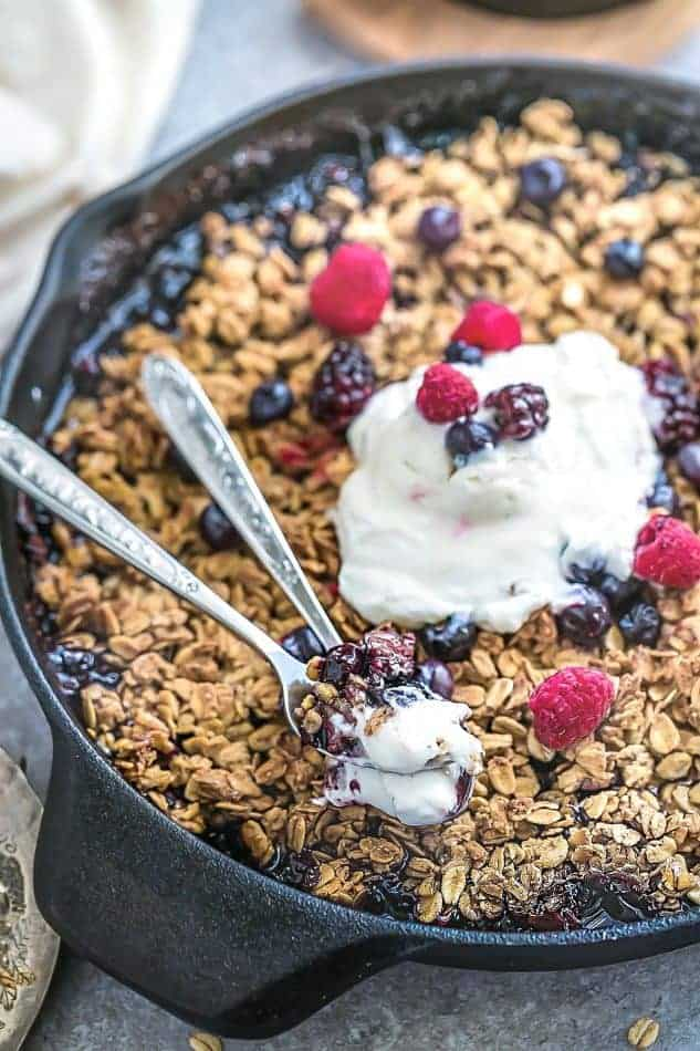 vegan fruit crisp in a cast iron pan topped with fresh mixed berries and whipped cream