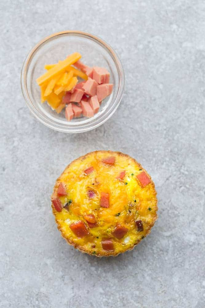 Top view of one muffin tin eggs with ham and cheese on a grey background