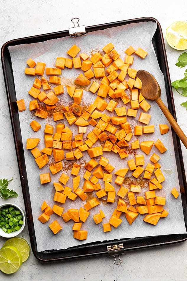 Overhead view of cubed seasoned sweet potatoes on a parchment-lined baking sheet
