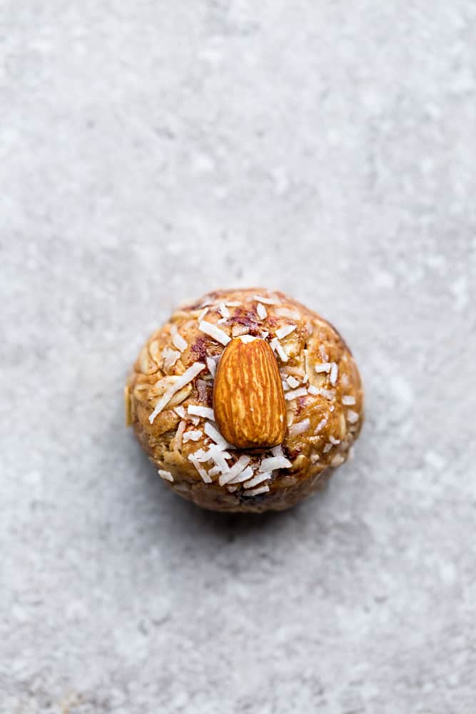 coconut almond butter energy ball coated in coconut flakes and topped with a whole almond