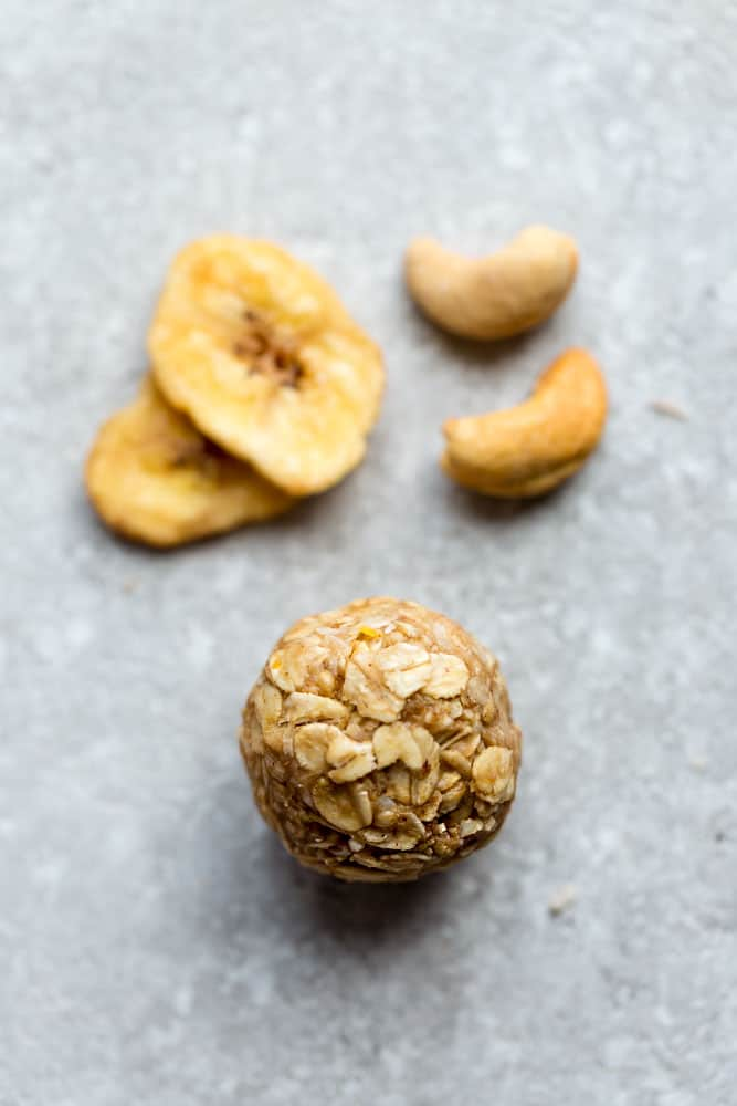 Close up view of Banana Nut Energy Bites with a hand holding it
