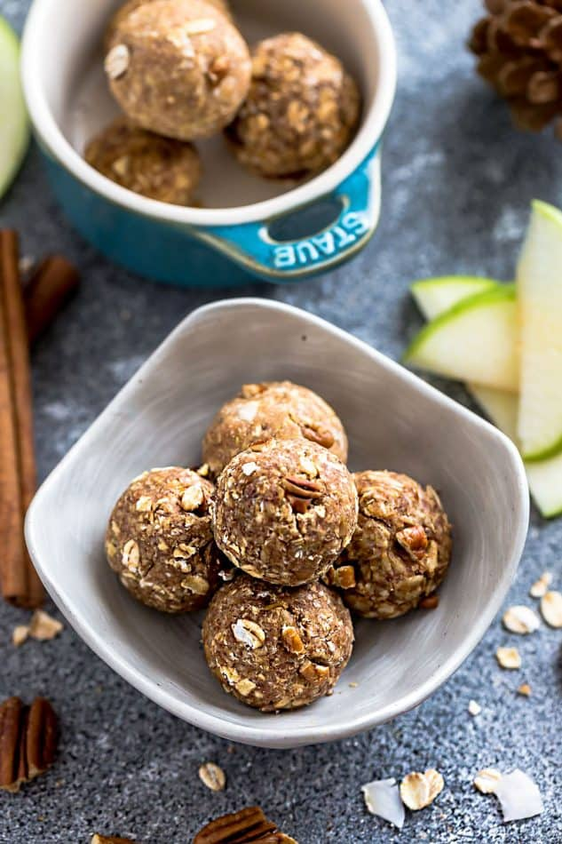 Apple Cinnamon No Bake Energy Bites with oats and pecans in a small white serving bowl on a blue table.