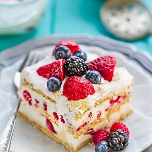 Top view of one slice of icebox cake on a white plate with a fork and mixed berries