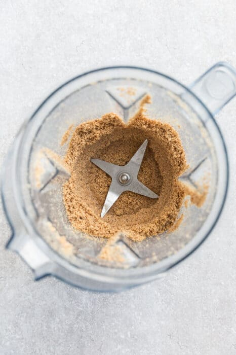 Top view of making nut butter in a Vitamix blender with a spoon on a grey background - crumbly texture