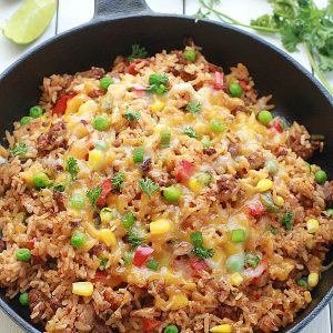 {One Pan} Mexican Rice Skillet - An easy Mexican rice dish made all in one pan in under 30 minutes. Perfect & easiest for weeknights with the best taco flavors. Even the rice made in same pan.