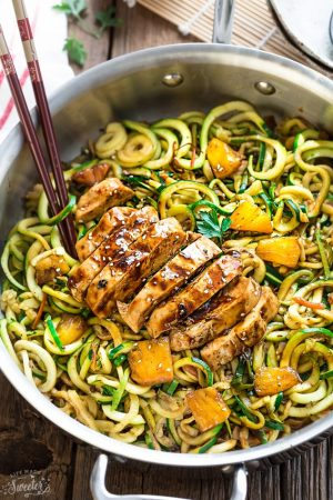 Healthy One Pot Sliced Teriyaki Chicken Zoodles with brown chopsticks in a large silver skillet on a wooden table.