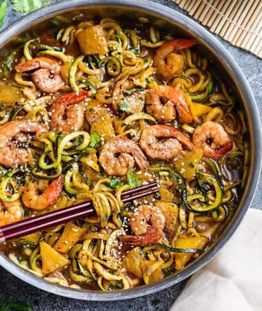 Close-up view of teriyaki shrimp with zucchini noodles in a stainless steel pan with chopsticks