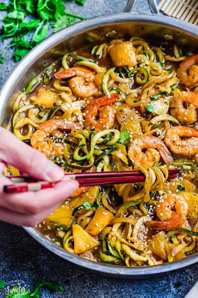 Close-up view of teriyaki shrimp with zucchini noodles in a stainless steel pan with a hand holding chopsticks