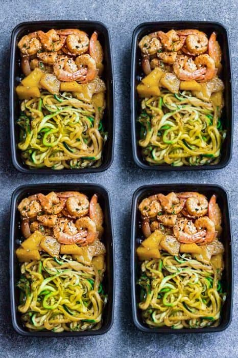 Top view of healthy shrimp teriyaki with zucchini noodles in four black meal prep containers on a grey background