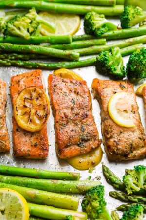 Top view of oven baked salmon on a baking sheet with asparagus and lemon