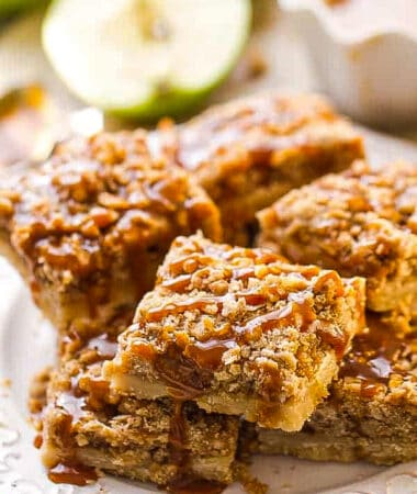 Side view of a pile of apple pie bars on a white plate