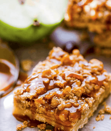 Top view of one vegan apple pie bar on a cutting board with paleo caramel sauce drizzled on top