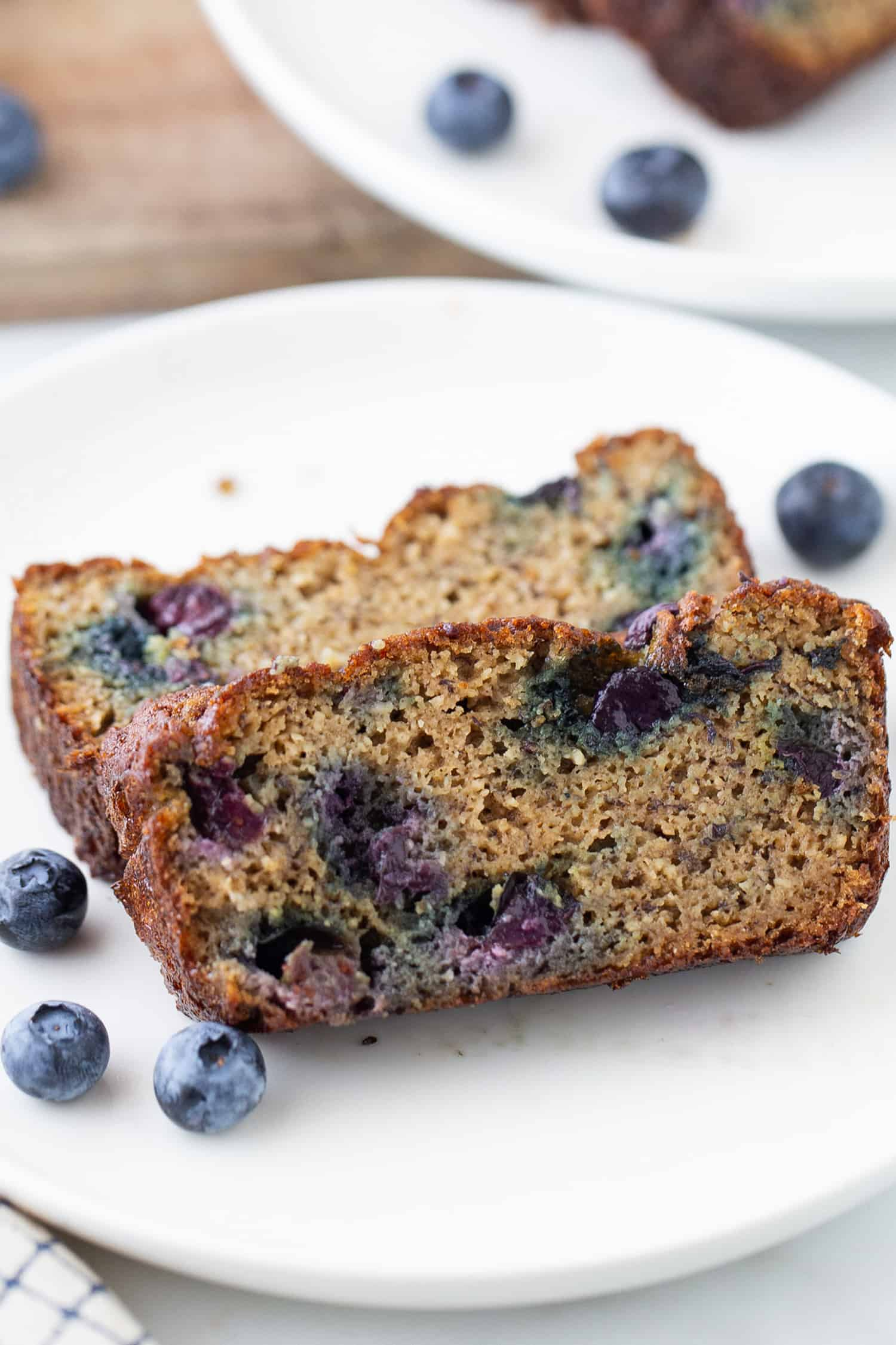 Top close-up view of two slices of blueberry banana bread on a white plate
