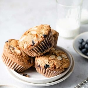 Side view of three paleo blueberry muffins on a white plate