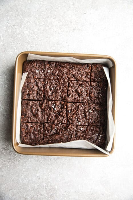 Top view of paleo brownies in a square baking pan a white backgroumd