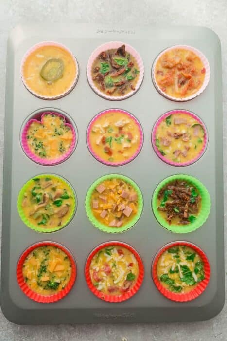 Top view of 12 silicone muffin liners with egg batter and topping variations in a muffin pan to make Egg Muffins